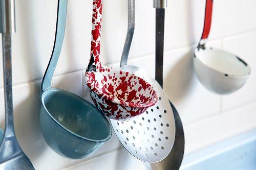 verschiedene Suppenkellen in Form & Farbe, hängen neben einander