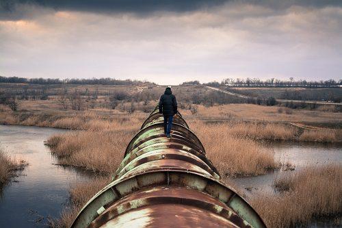 Mensch läuft auf Wasserrohr, im Hintergrund Wasserlandschaft